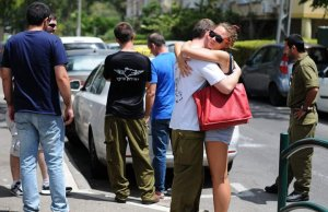Reserve soldier says farewell to his girlfriend at a mobilization point in Haifa. Photo by Rami Shalosh, Ha'aretz online, 18 July 2014.