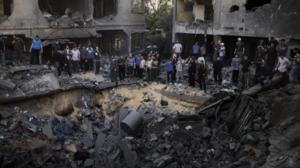 Palestinian men gather around a crater caused by an Israeli air strike on the al-Dalu family's home in Gaza City on November 18, 2012. (AFP Photo / Marco Longari)