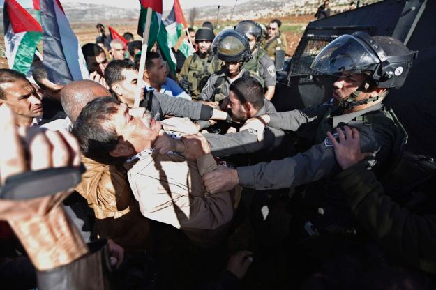 Palestinian minister Ziad Abu Ein, left, scuffles with an Israeli border policeman near the West Bank city of Ramallah on Wednesday. Photo: Mohamad Torokman, Reuters