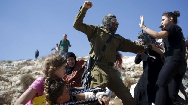 Palestinians scuffle with an Israeli soldier as they try to prevent him from detaining a boy during a protest against Jewish settlements in the West Bank village of Nabi Saleh, near Ramallah. Reuters